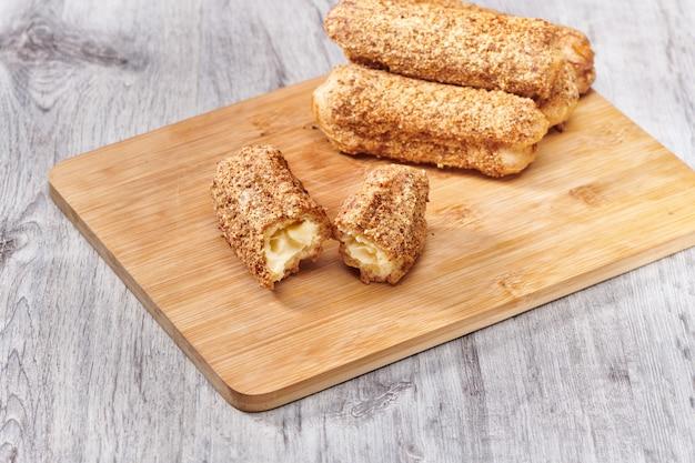Вкусные французские эклеры на деревянном столе. вкусный десерт. домашний торт эклеры. сладкое десертное тесто с кремовой начинкой.