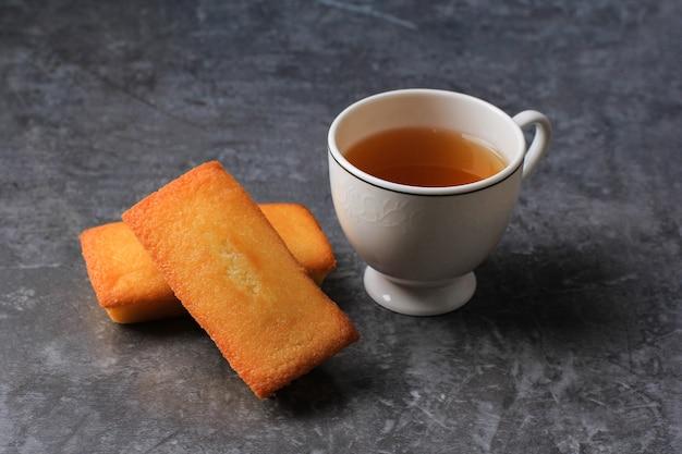 新鮮なバターとお茶を添えたおいしいフランスのフィナンシェケーキ