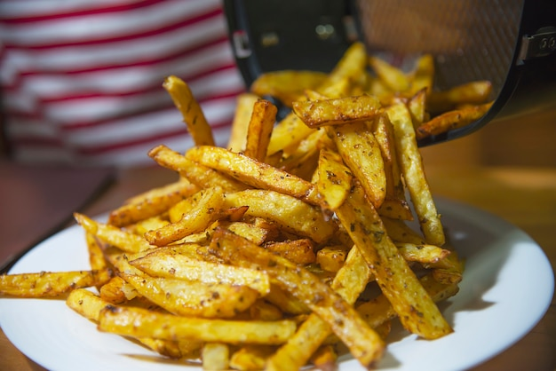 Delicious french fried potato mix with chilly powder on wooden table