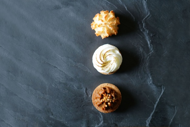 Delicious french mini cakes lined up on black slate with text space