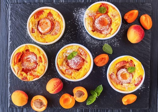 Вкусный французский летний десерт - запеченные абрикосовые клафути в формочки на черном сланцевом подносе, на деревянном столе, вид сверху, плоская планировка