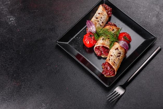 暗い背景に黒い正方形のプレートにトーストとおいしい新鮮な牛肉のタルタル