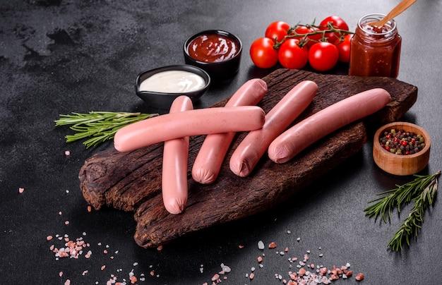 Вкусные свежие вареные колбаски с овощами и специями на темном фоне бетона