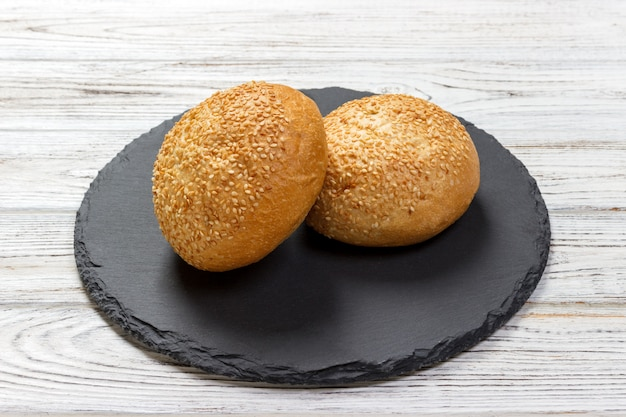 Delicious fresh buns with sesame seeds on a slate board. top view