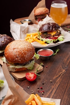 Delicious fresh burger with lettuce, cheese, onion, tomato on a rustic wooden board on a brown background. also fries in craft paper, ketchup and beer. vertical shot.