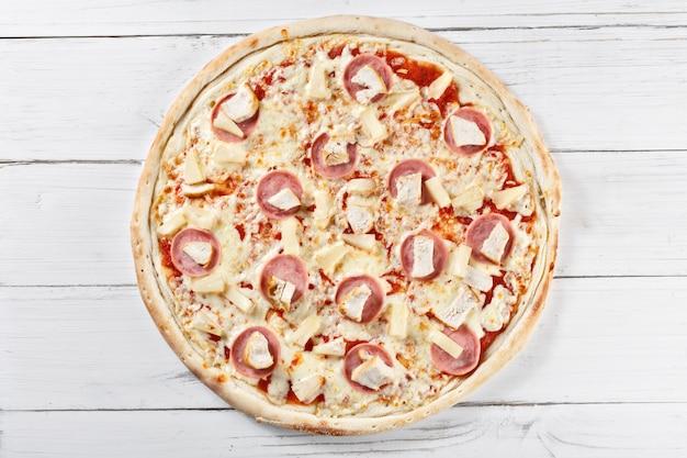 木製のテーブルで提供していますチキンとパイナップルのおいしい新鮮なチキタピザ