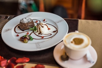 Delicious fresh chocolate dessert and cup of beverage in restaurant