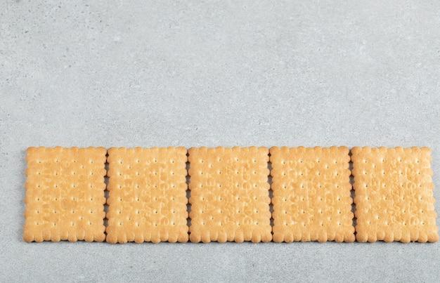 Deliziosi cracker freschi su uno sfondo grigio.
