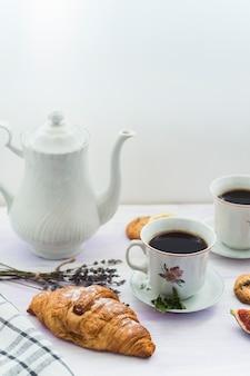 ティーポットとテーブルの上にコーヒーが入ったおいしい新鮮なクロワッサン
