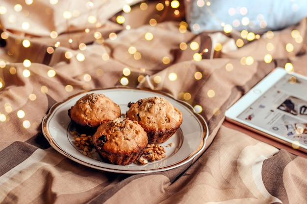 Delicious fresh cupcake with nut on a plate in bed.