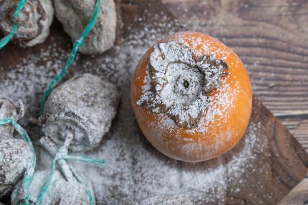 Deliziosi frutti di cachi freschi e secchi su tavola di legno