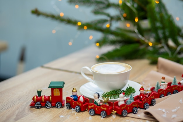 Delicious fresh festive morning cappuccino coffee in a ceramic white cup on the wooden table with decorative christmas train, red ornamentals, fireflies and spruce branches.