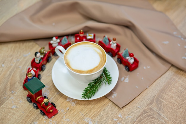 Delicious fresh festive morning cappuccino coffee in a ceramic white cup on the wooden table with decorative christmas train, red ornamentals, fireflies and spruce branches