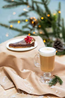 Delicious fresh festive morning cappuccino coffee in a glass cup and cupcake dessert on the wooden table, fireflies and spruce branches