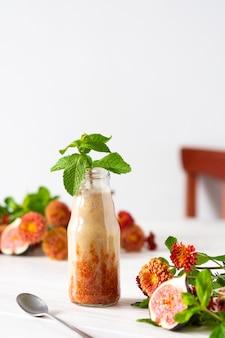 ガラスの瓶に入ったおいしい新鮮で健康的なフルーツのスムージー、メロンとバナナのイチジク、ミントの秋の菊の花