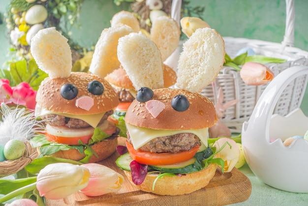 イースターキッズパーティーのためのおいしい新鮮な自家製バニーバーガー。面白いウサギの銃口と耳、イースターの装飾のコピースペースを備えたウサギの形の創造的なハンバーガー