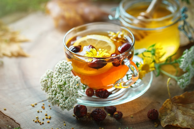 Delicious fresh honey and a cup of healthy tea with lemon and rose hips