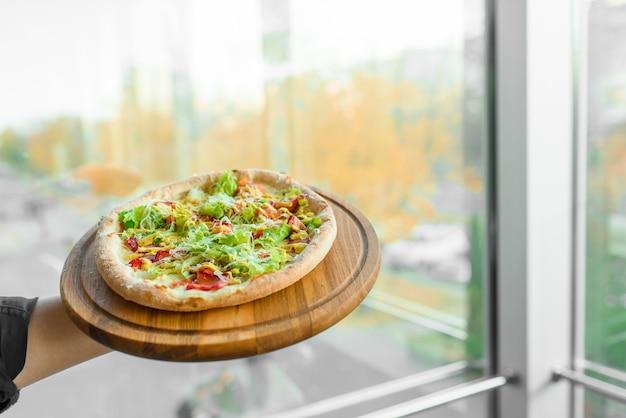 나무 보드에 햄, 살라미 소시지, 토마토, 샐러드, 치즈와 함께 맛있는 신선한 이탈리아 피자