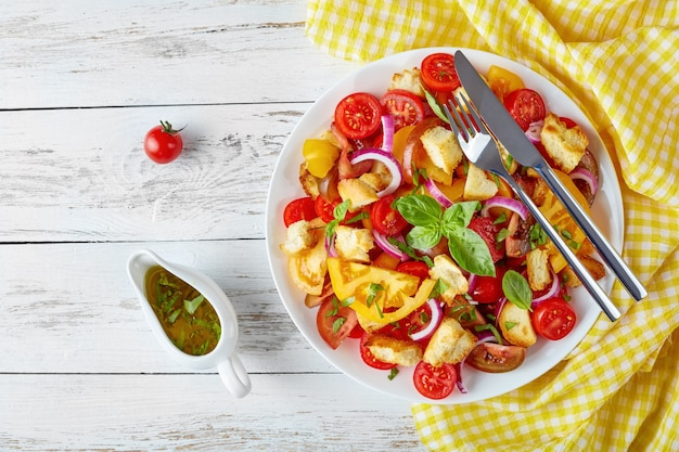 Delicious fresh italian salad panzanella with tomatoes, croutons and onion rings on a white plate on a wooden table with napkin, view from above, flat lay