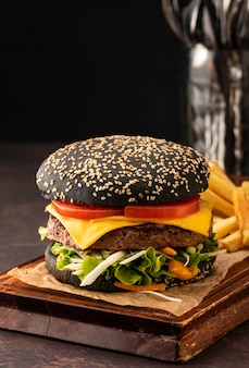 Delicious fresh juicy homemade cheeseburger in a black bun with tomatoes and salad