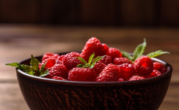 어두운 테이블에 맛있는 신선하고 육즙이 많은 빨간 라즈베리. 제철 딸기와 과일