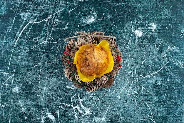 화려한 배경에 맛있는 신선한 머핀과 크리스마스 화환. 고품질 사진