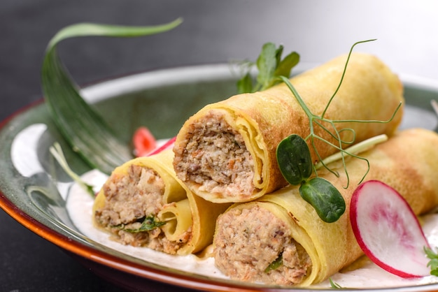 Вкусные свежие блины с мясом на тарелке с зеленью и редисом. вкусный сытный завтрак
