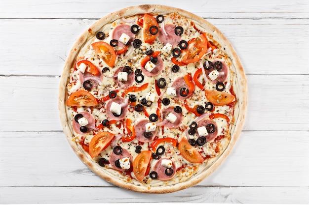 おいしい新鮮なピザを木製のテーブルで提供しています。上面図。