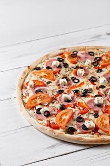 木製のテーブルで提供していますおいしい新鮮なピザ