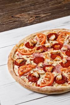 木製のテーブルで提供していますチキンハムトマトのおいしい新鮮なピザ