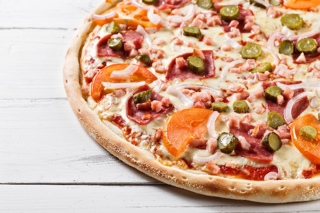 Delicious fresh pizza with ham and gherkin served on wooden table
