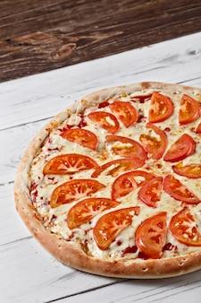 トマトとチーズのおいしい新鮮なピザを木製のテーブルで提供しています