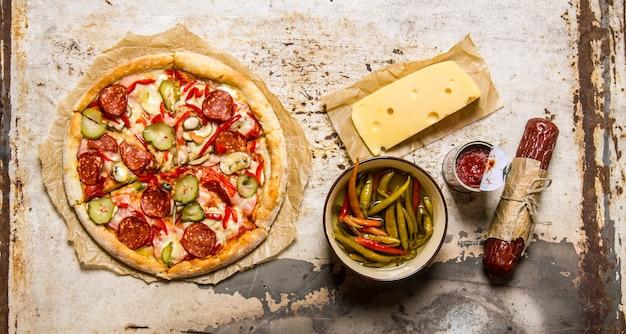 トマトソース、ペパロニ、ペパロニ、チーズが入ったおいしいフレッシュピザ。素朴な背景に。上面図