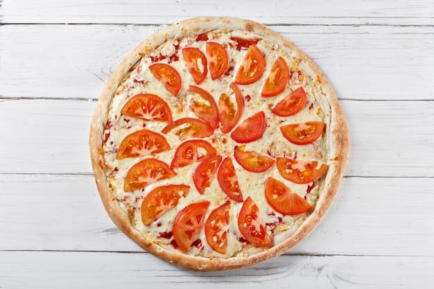 木製のテーブルで提供していますトマトのおいしい新鮮なピザ。上面図。