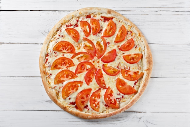 Delicious fresh pizza with tomato served on wooden table. top view.