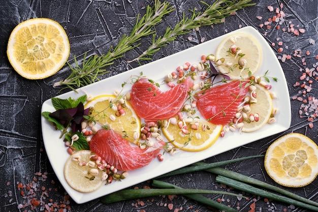 Вкусный свежий сырой тунец на белой тарелке с кусочками лимона, зеленью и розмарином на заднем плане, вид сверху, крупный план.