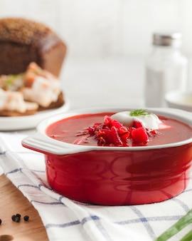 Вкусный свежий красный борщ из темного хлеба с салом и солью на кухонном столе Premium Фотографии