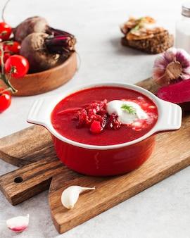 Вкусный свежий красный борщ, чеснок, помидоры и свекла на кухонном столе Premium Фотографии