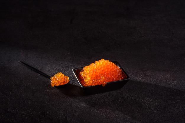 暗いコンクリートのテーブルの上においしい新鮮な赤キャビア。美味しくてボリュームたっぷりの朝食