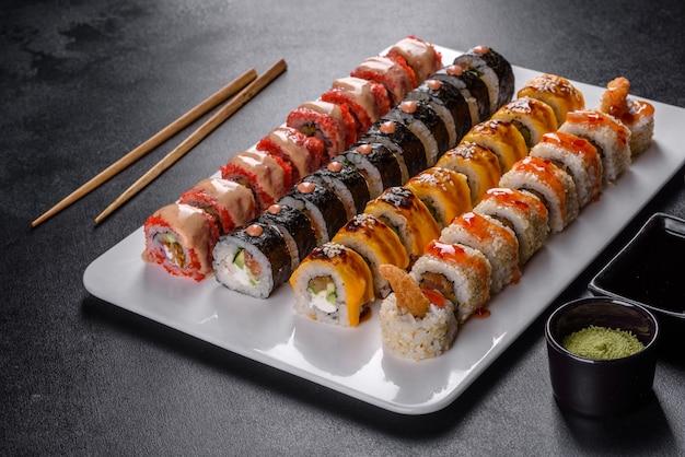 다양한 세트의 맛있는 신선한 롤. 아보카도, 새우, 게, 연어를 곁들인 일본 음식