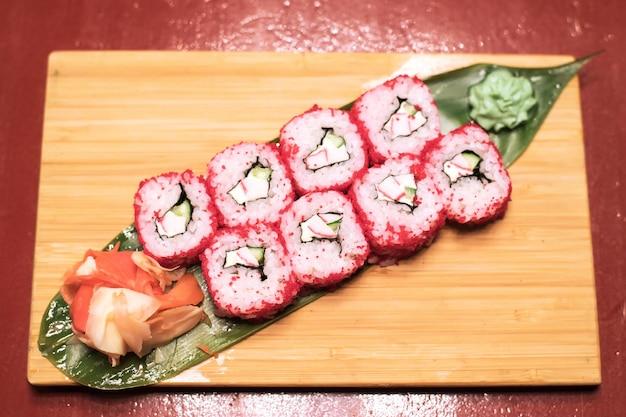 Вкусные свежие роллы с листьями салата из сливочного сыра из красной рыбы на деревянной тарелке