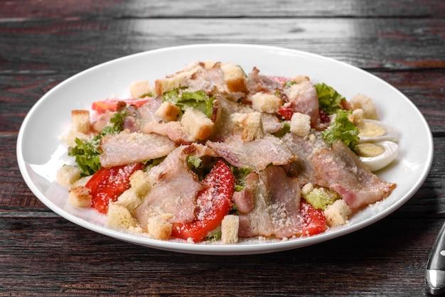 향신료와 채소를 곁들인 베이컨과 토마토를 곁들인 맛있는 신선한 샐러드. 축제 가족 테이블 준비