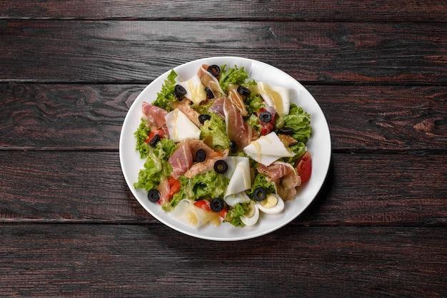 축제 테이블에 베이컨과 함께 맛있는 신선한 샐러드. 가족 휴가 준비