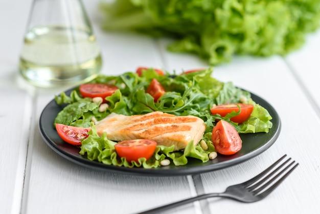 생선, 토마토, 양상추와 함께 맛있는 신선한 샐러드 나뭇잎. 건강한 음식
