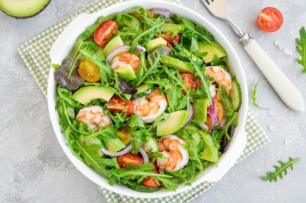 Вкусный свежий салат с креветками, помидорами, авокадо, огурцом и луком в миске на сером фоне бетона. здоровое блюдо. вид сверху, копия пространства.