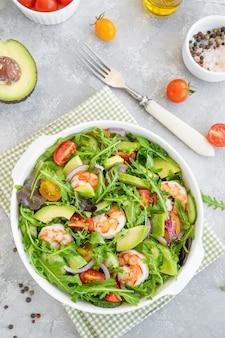 Вкусный свежий салат с креветками, помидорами, авокадо, огурцом и луком в миске
