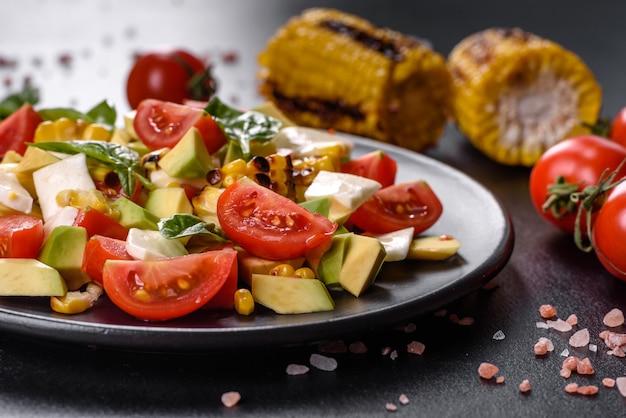 トマト、アボカド、チーズ、焼きトウモロコシとオリーブオイルのおいしいフレッシュサラダ。地中海料理