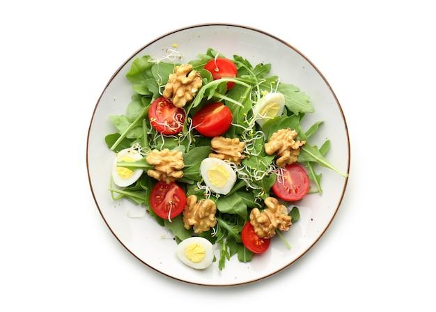白で隔離、プレートにクルミとおいしい新鮮なサラダ