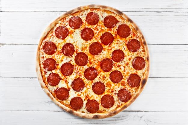 木製のテーブルで提供するおいしい新鮮なサラミのピザ。上面図。