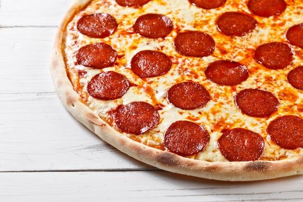 木製のテーブルで提供するおいしい新鮮なサラミのピザ